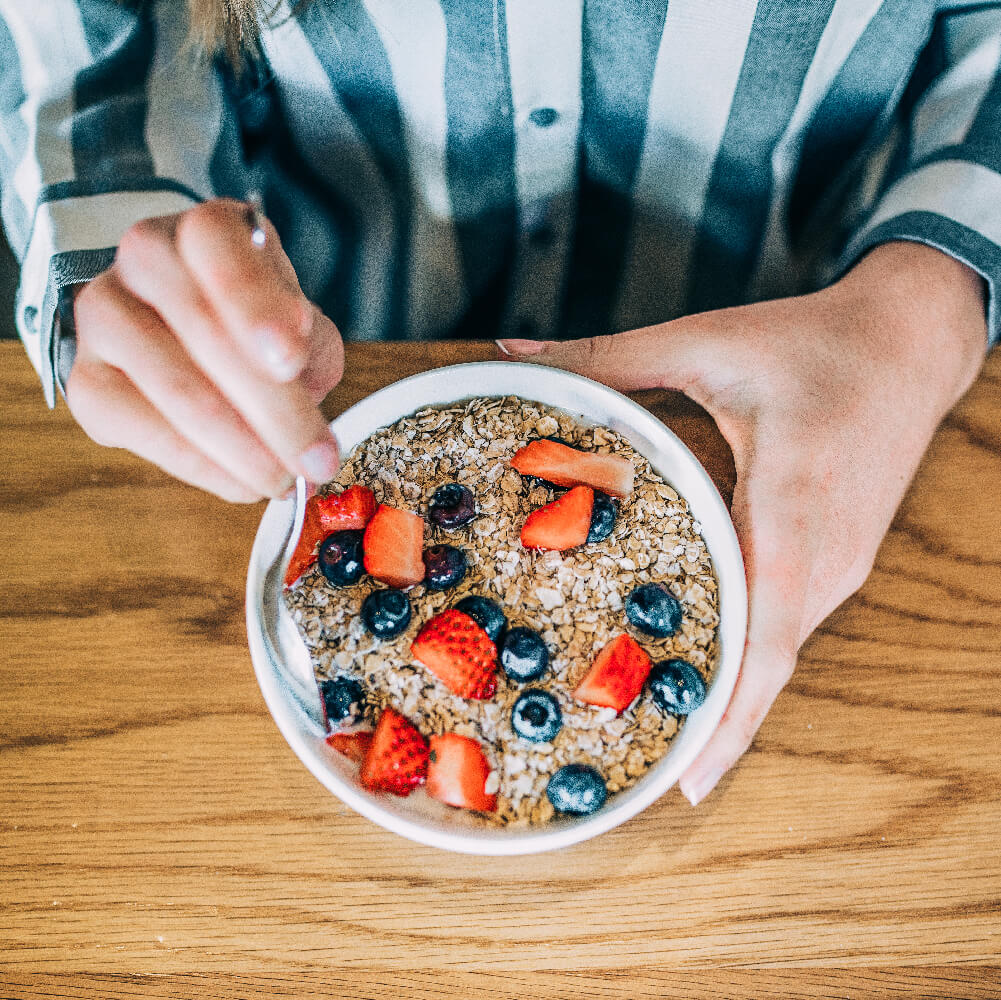 Person eating Eco Valley Hearty Oats